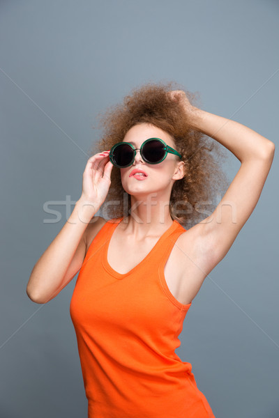 Attractive curly female in sunglasses posing and biting bottom lip Stock photo © deandrobot