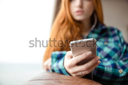 Closeup of cellphone is used by pensive young redhead woman  Stock photo © deandrobot
