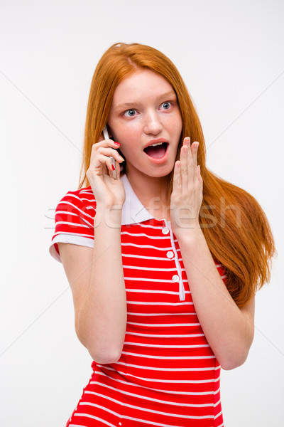 Amazed excited redhead woman talking on mobile phone Stock photo © deandrobot