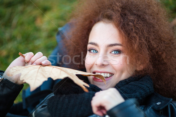 Woman with curly hair holding yellow leave Stock photo © deandrobot