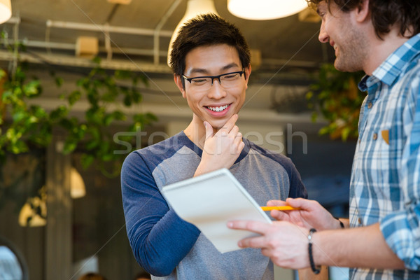 Happy cheerful smart handsome students making notes in notepad together Stock photo © deandrobot