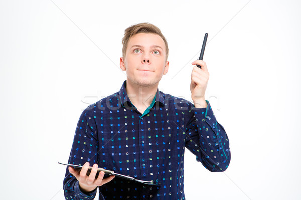 Concentrated handsome man holding clipboard and pointing up by pen Stock photo © deandrobot