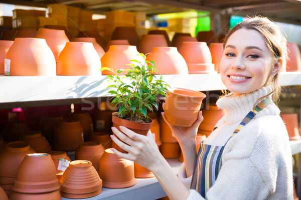 Happy woman gardener buying new pot for plant Stock photo © deandrobot