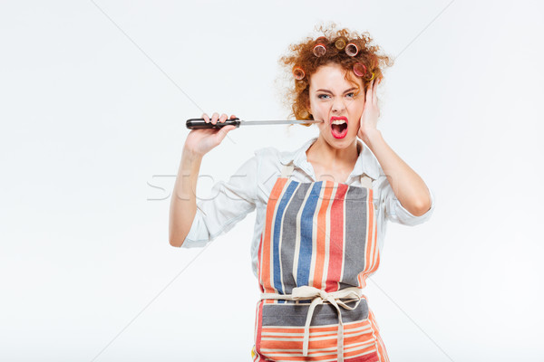 Curly housewife in striped apron holding and playing with knife  Stock photo © deandrobot