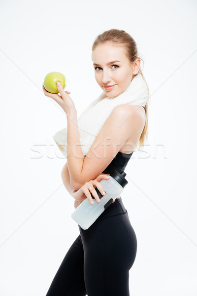 Woman athlete with towel holding bottle of water and apple  Stock photo © deandrobot
