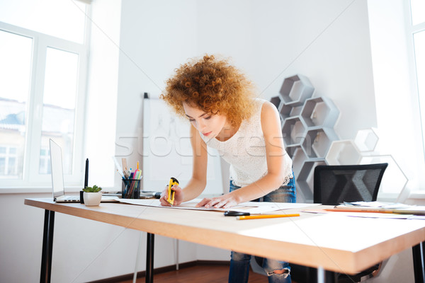Serious woman photographer with curly red hair working in office Stock photo © deandrobot