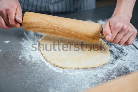 Hands of cook using wooden rolling pin for dough  Stock photo © deandrobot