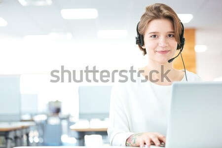 Happy young woman sitting and working with laptop using headset  Stock photo © deandrobot
