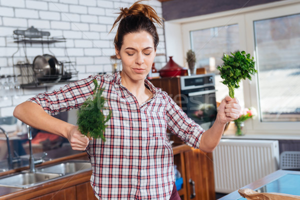 Happy woman holding dill and dacing on the kitchen Stock photo © deandrobot