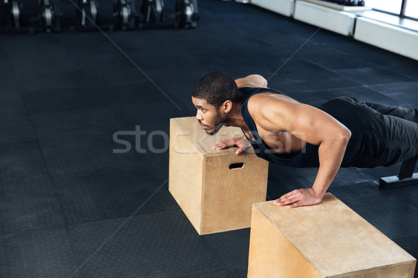 Young Healthy Athlete Doing Push Ups at the gym Stock photo © deandrobot