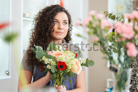 Focused woman florist working and making flower bouquet in shop Stock photo © deandrobot