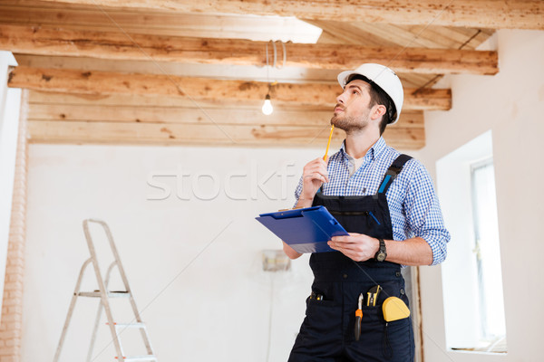 Young specialist builder examines his working space Stock photo © deandrobot