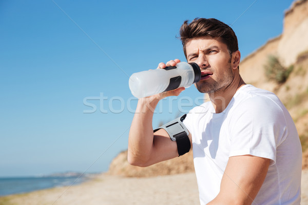 Sportsman sitting and drinking water on the beach Stock photo © deandrobot