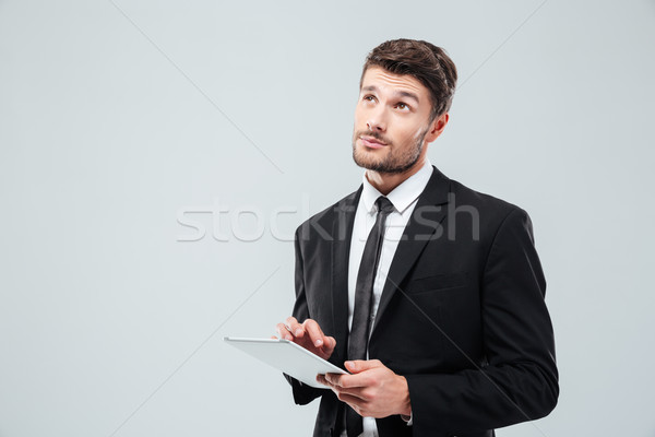 Portrait of pensive young businessman thinking and using tablet Stock photo © deandrobot