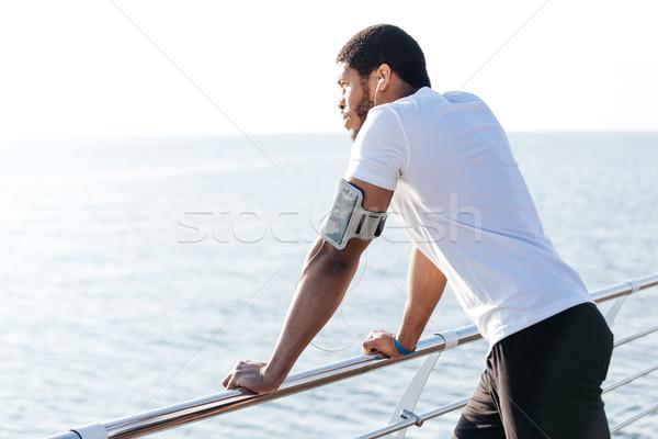 Hombre escuchar música pensando muelle Foto stock © deandrobot