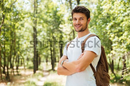 Smiling young man with backpack walking in forest Stock photo © deandrobot