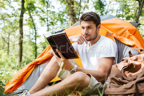 Thoughtful young man tourist sitting and reading book in forest Stock photo © deandrobot