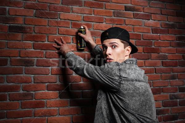 Graffiti man in cap spraying brick wall by aerosol can Stock photo © deandrobot