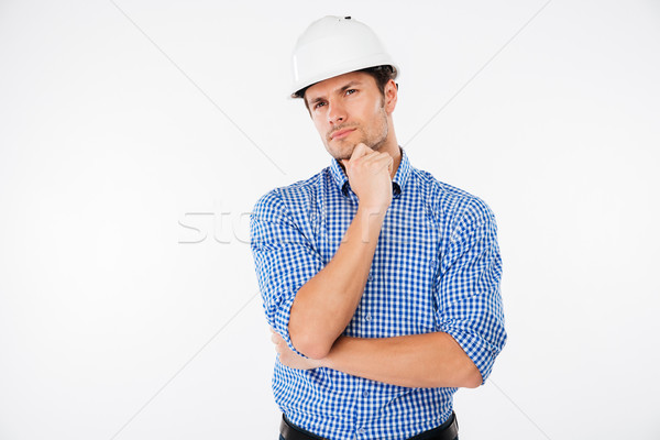 Pensive young man builder in hard hat standng and thinking Stock photo © deandrobot