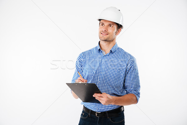 Man building engineer in hard hat writing on clipboard Stock photo © deandrobot