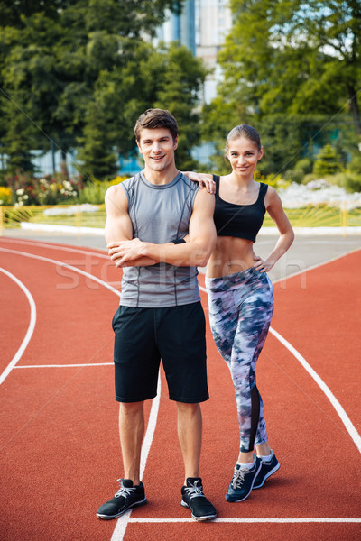Young man and woman standing on athletics race track Stock photo © deandrobot