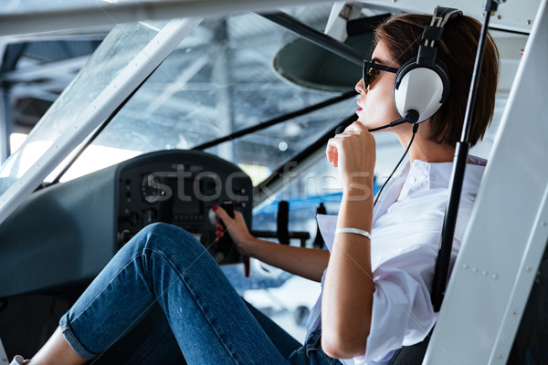Woman pilot sitting and talking with headset in small plane Stock photo © deandrobot