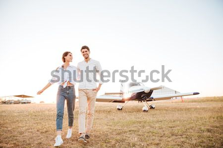 Couple walking together across the field at sunset Stock photo © deandrobot