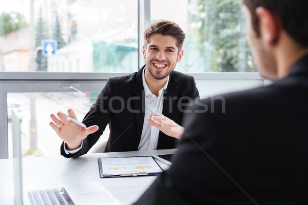 Dwa szczęśliwy młodych biznesmenów posiedzenia pracy Zdjęcia stock © deandrobot