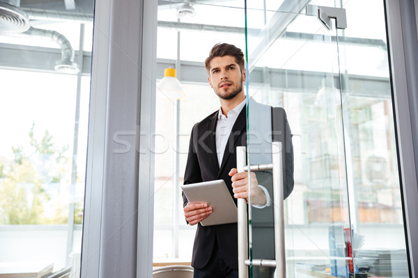 Businesman with tablet entering the door in office Stock photo © deandrobot