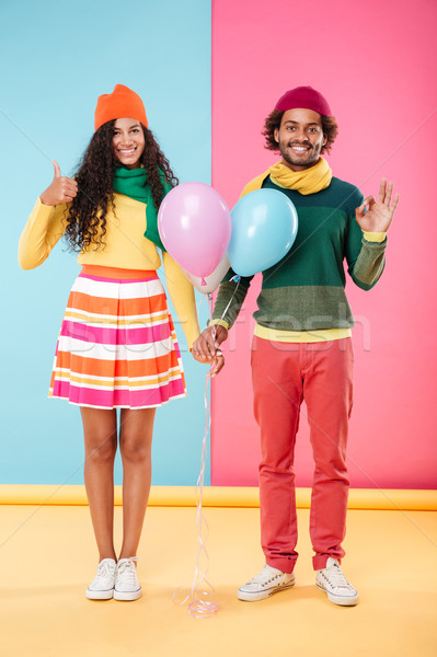 Smiling couple with balloons showing thumbs up and ok sign Stock photo © deandrobot