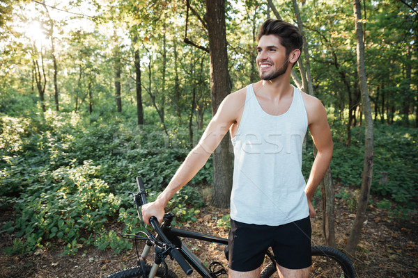 Happy cyclist in forest Stock photo © deandrobot
