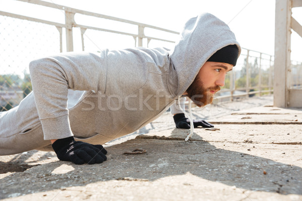 Concentrated sports man doing push ups outdoors Stock photo © deandrobot