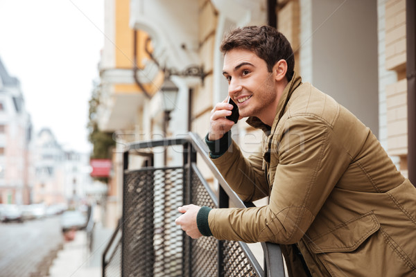 Happy young man walking on the street talking by phone. Stock photo © deandrobot