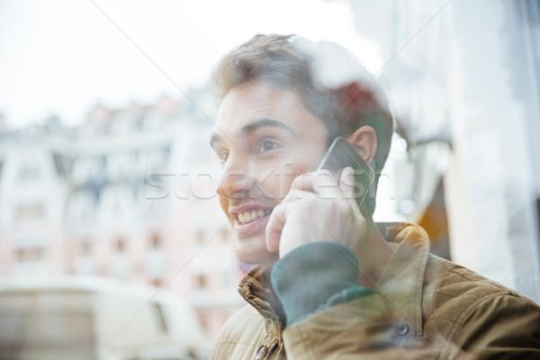 Joyful man walking on the street and talking by phone. Stock photo © deandrobot