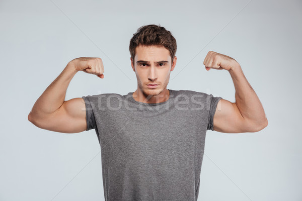 Man flexing both biceps and looking at camera Stock photo © deandrobot