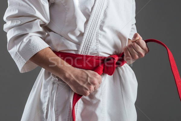 Cropped photo of young sportsman tightening red belt Stock photo © deandrobot
