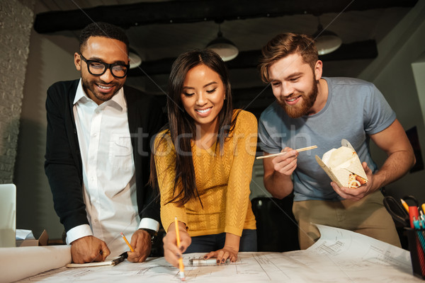 Cheerful architects working at night while eating Stock photo © deandrobot