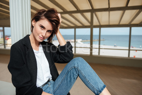 Smiling woman sitting in arbour near the sea Stock photo © deandrobot