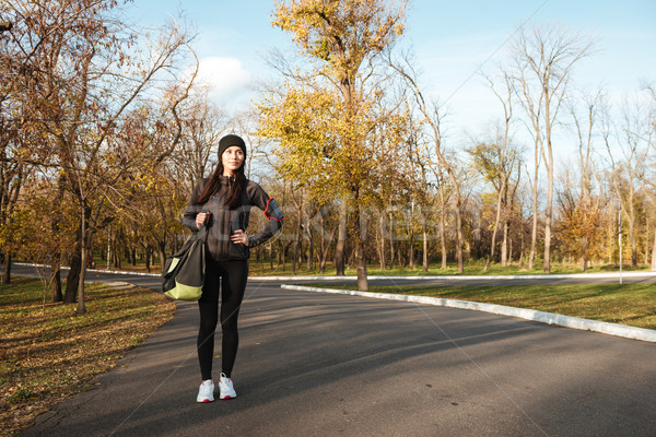 Woman runner in warm clothes and earphones in autumn park Stock photo © deandrobot