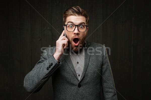 étonné étonné homme lunettes parler téléphone portable Photo stock © deandrobot