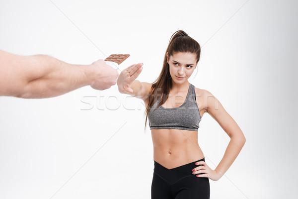 Determined fitness woman refusing to take chocolate from somebodys hand Stock photo © deandrobot