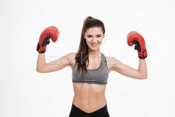Stock photo: Satisfied sports woman wearing boxing gloves and showing biceps