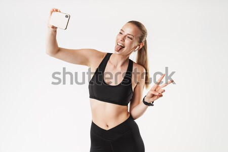 Happy woman making selfie photo on smartphone and showing biceps Stock photo © deandrobot