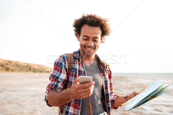 Smiling african man using map and cell phone outdoors Stock photo © deandrobot