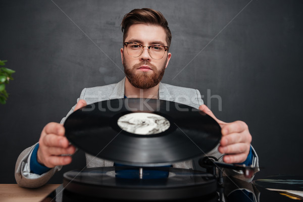 Portrait of man in glasses using turntable and vinyl record Stock photo © deandrobot