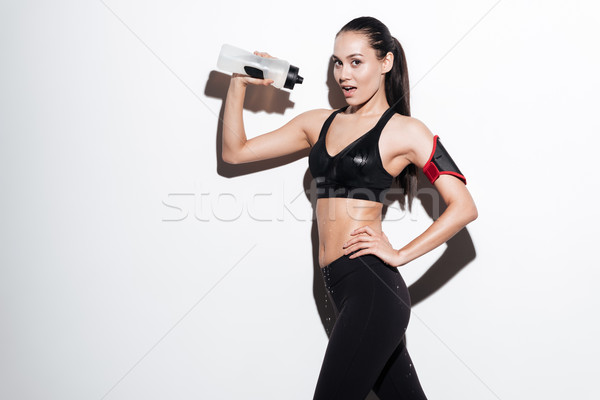 Happy alluring woman athlete pouring water from bottle on herself Stock photo © deandrobot