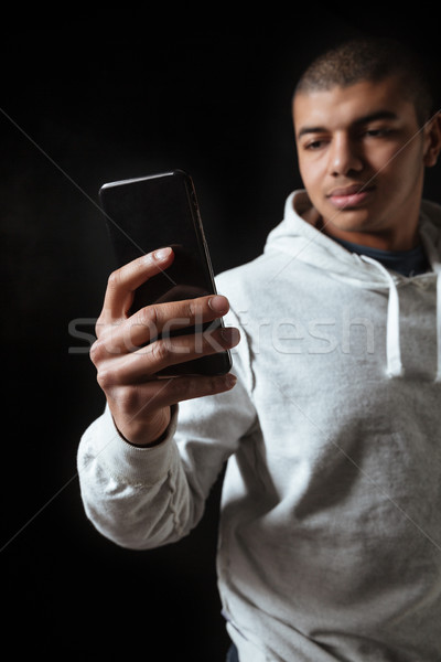 Handsome african young man athlete in hoodie using mobile phone Stock photo © deandrobot