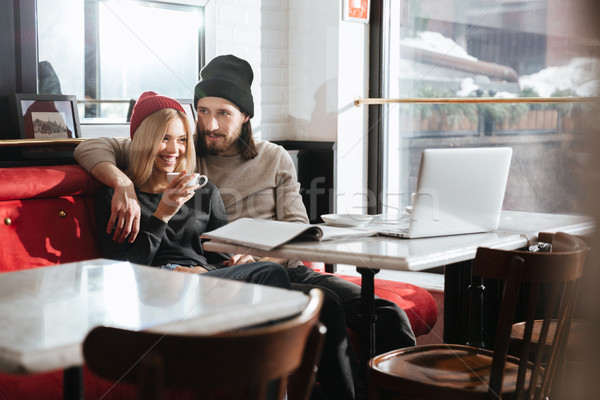 Side view of hipsters sitting with laptop in cafe Stock photo © deandrobot