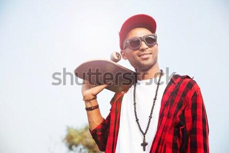 Attractive dark skinned man holding skateboard Stock photo © deandrobot