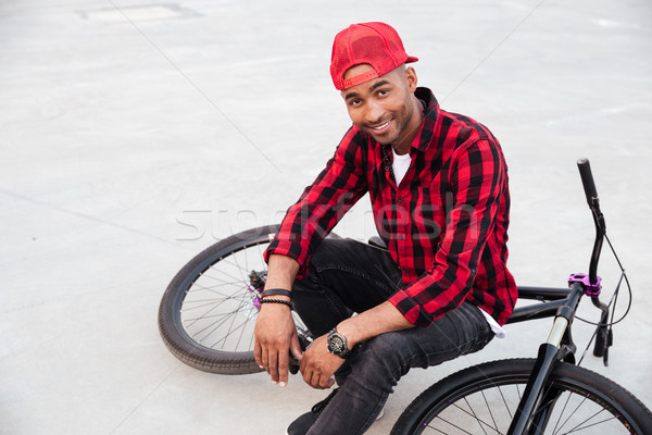 Happy dark skinned boy wearing cap sitting on his bicycle Stock photo © deandrobot